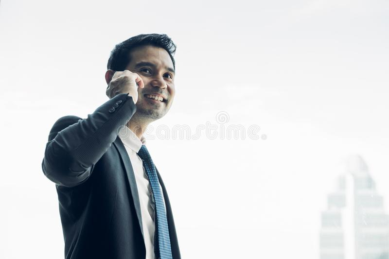 Businessman using mobile phone near office window at office building,communication concept stock photo