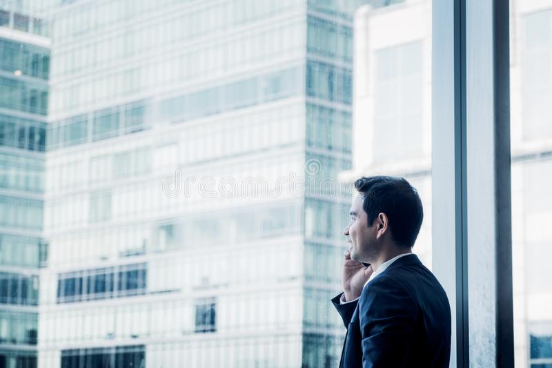 Businessman using mobile phone near office window at office building,communication concept,blue color tone. royalty free stock photos
