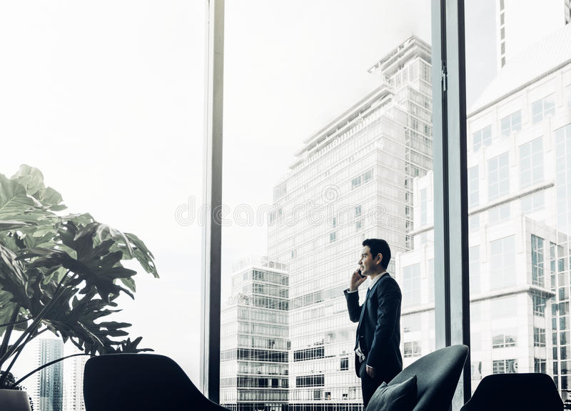 Businessman using mobile phone near office window at corridor ar stock image