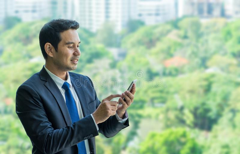 Businessman using mobile phone near office window at office building,communication concept stock image
