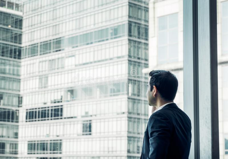 Businessman using mobile phone near office window at office building,communication concept,vintage filter royalty free stock images
