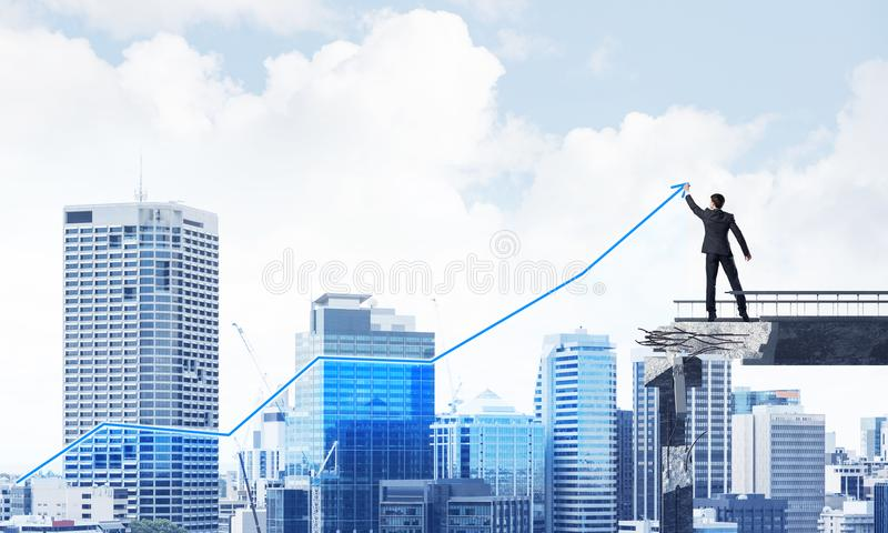 Businessman using modern media interface. Businessman in suit drawing graphs on modern statistical media interface while standing on broken bridge with stock photos