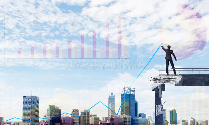Businessman using modern media interface. Businessman in suit drawing graphs on modern statistical media interface while standing on broken bridge with stock photography