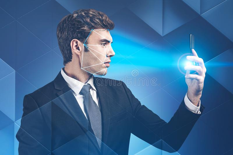 Businessman using phone with facial recognition stock photography