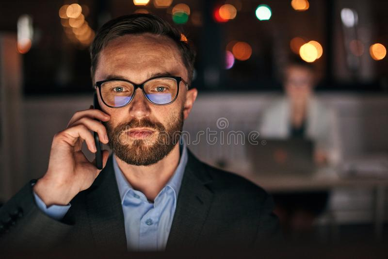 Businessman using phone late night royalty free stock photos