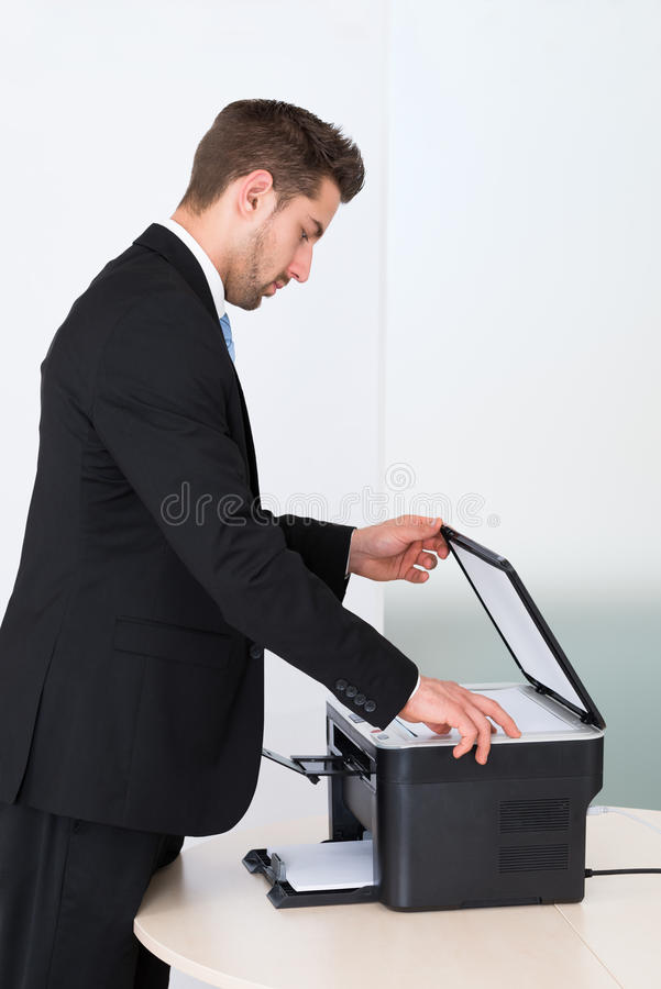 Businessman Using Photocopy Machine In Office royalty free stock photos