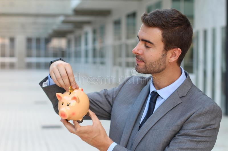Businessman using a piggybank to save money royalty free stock images