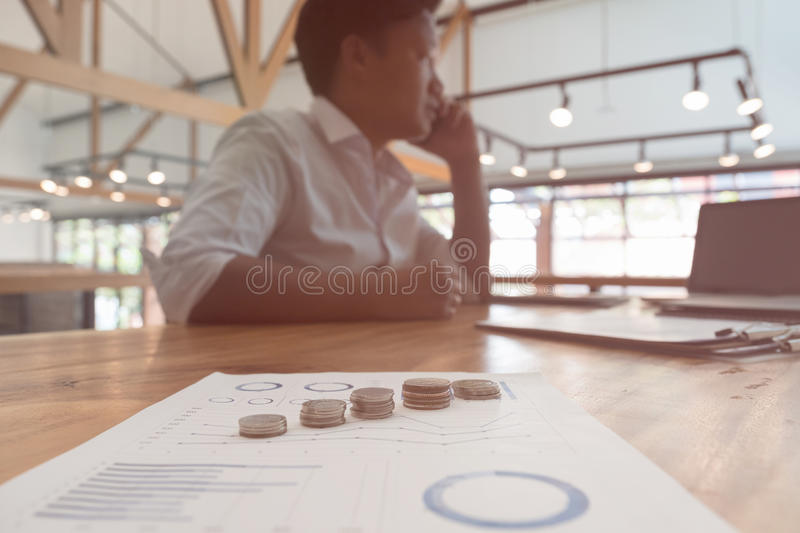 Businessman using smart phone with money coin and accounting graph and chart on table at office. growth of financial income from stock photo