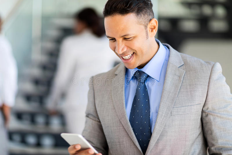 Businessman using smart phone. Professional businessman using smart phone in office royalty free stock photo