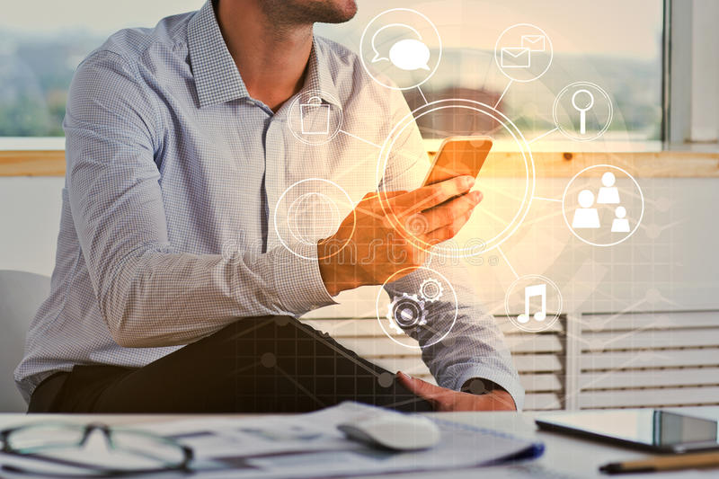 Businessman using smartphone with business diagram. Attractive young businessman using smartphone with circular business diagram at workplace. Communication royalty free stock photography