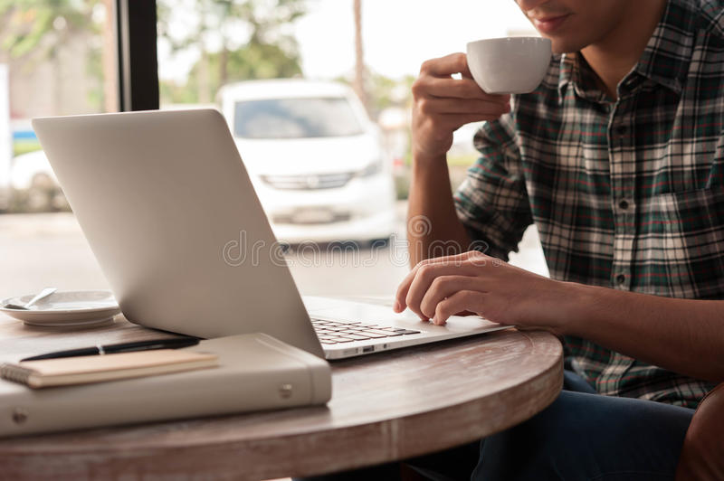Businessman using smartphone and laptop drinking a cup of coffee stock photography