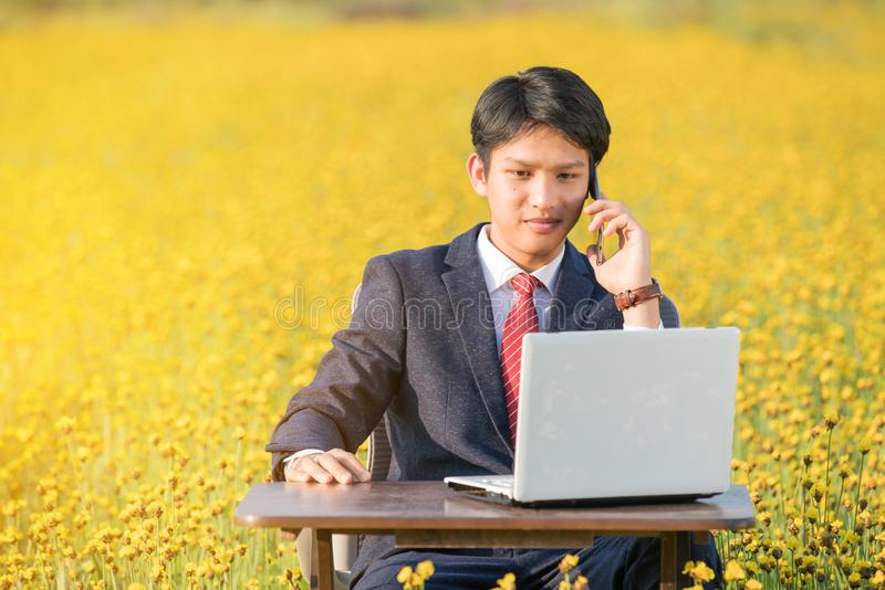Businessman using smartphone and laptop in flower field royalty free stock image