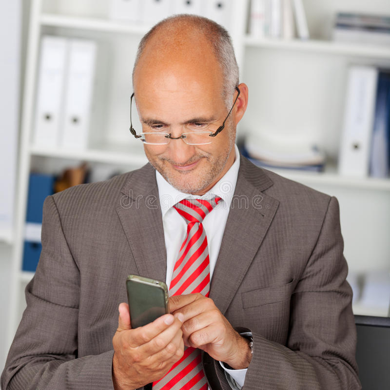 Businessman using smartphone in the office stock images