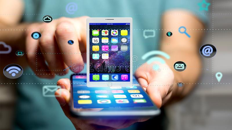 Businessman using a smartphone with a tablet surrounding by app stock illustration