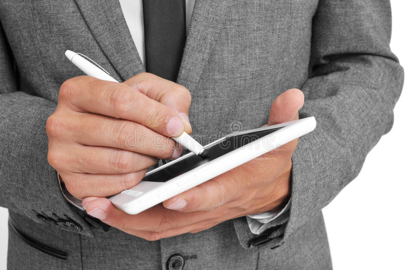 Businessman using a stylus pen in his tablet. A businessman using a stylus pen in his tablet royalty free stock photos
