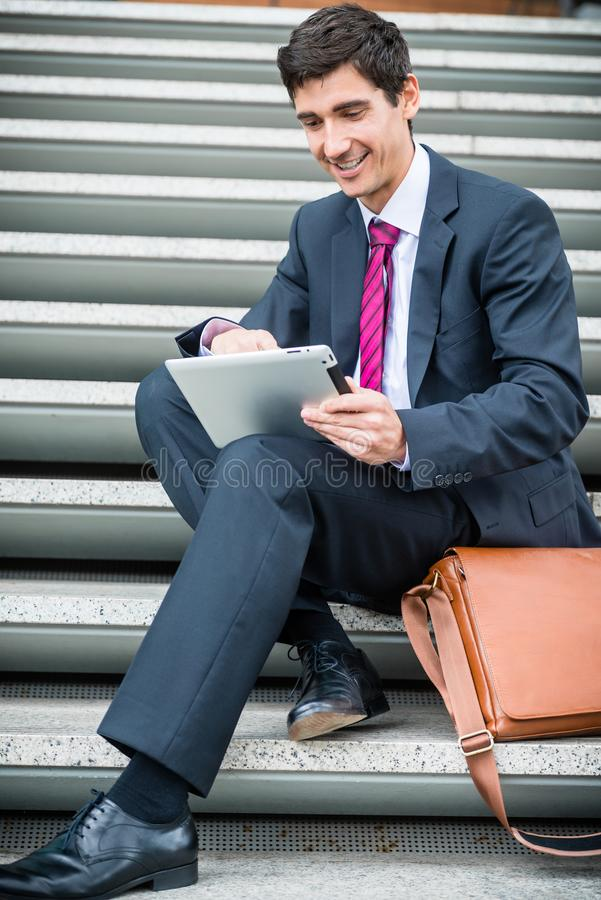 Businessman using a tablet for communication or data storage out. Young businessman smiling while using a tablet PC for online communication or data storage stock photography