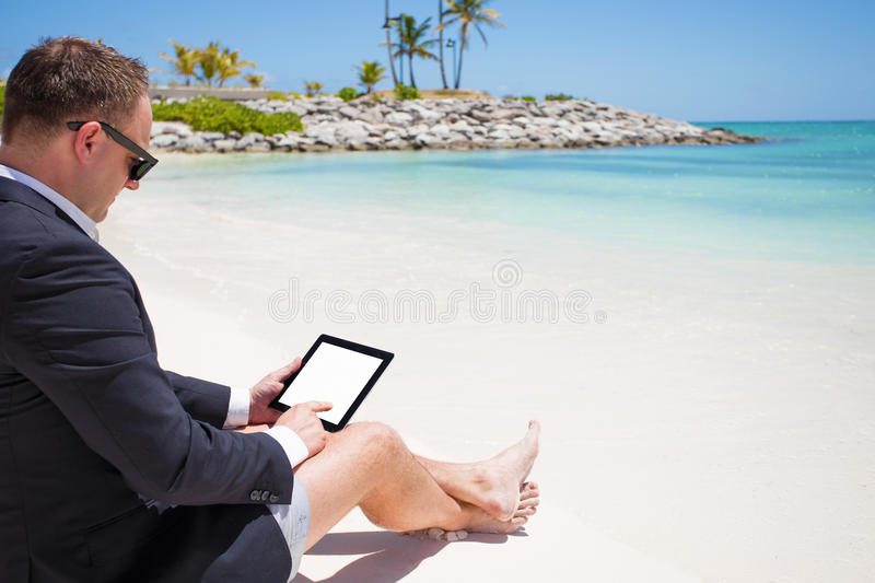 Businessman using tablet computer on the beach stock image
