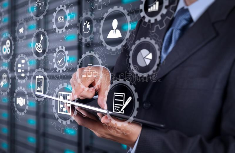 Businessman using tablet computer and server room background. AR virtual screen dashboard with project management with icons of scheduling, budgeting royalty free stock photos
