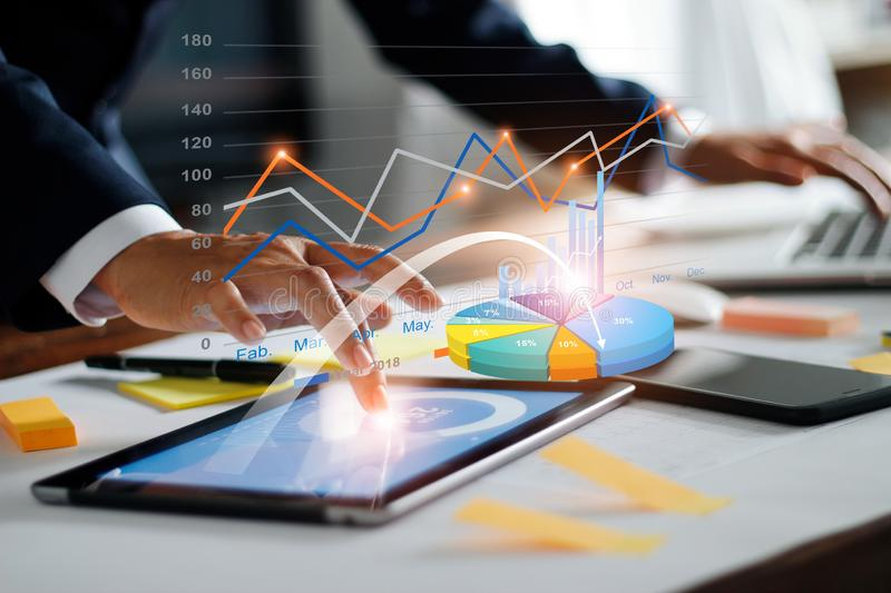 Businessman using tablet and laptop analyzing sales data and economic growth graph chart. Business strategy. Digital marketing. Business innovation technology stock image
