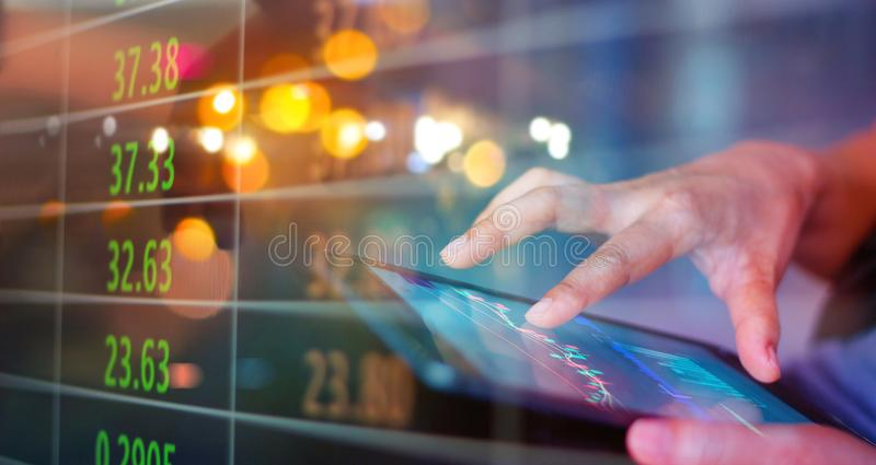 Businessman using tablet at night time Stock market. Businessman using a mobile device checking market data and currency exchange stock images