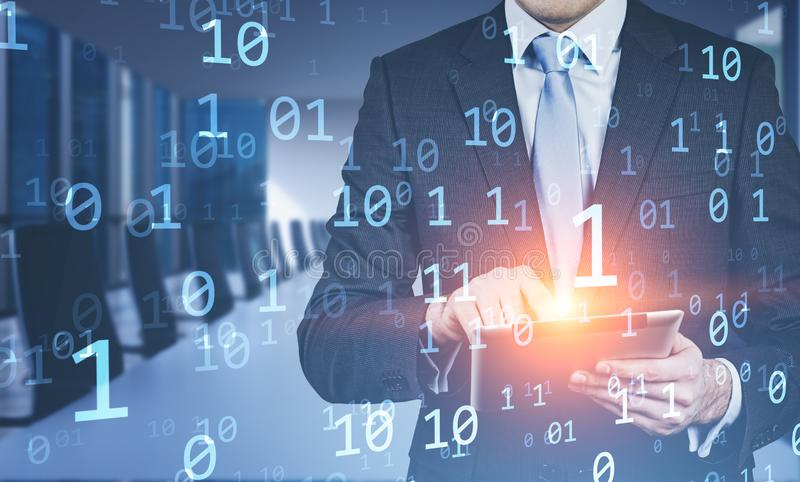 Businessman using tablet in office, binary numbers. Businessman using laptop in blurred office with double exposure of binary numbers. Concept of big data and stock image