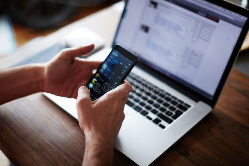 Businessman using technology sitting at modern loft wooden desk royalty free stock photo