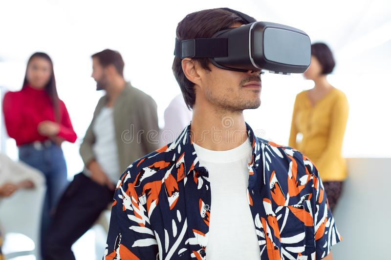 Businessman using virtual reality headset in a modern office. Front view of young Caucasian businessman using virtual reality headset in a modern office stock images
