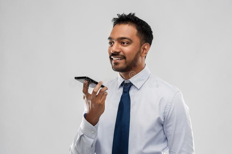 Businessman using voice command on smartphone stock photography