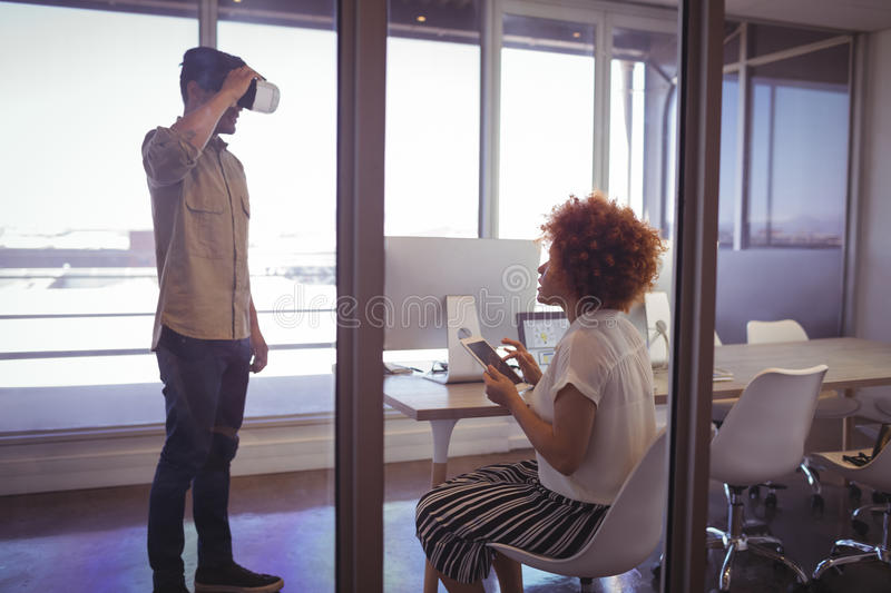 Businessman using VR glasses with businesswoman in office royalty free stock photos