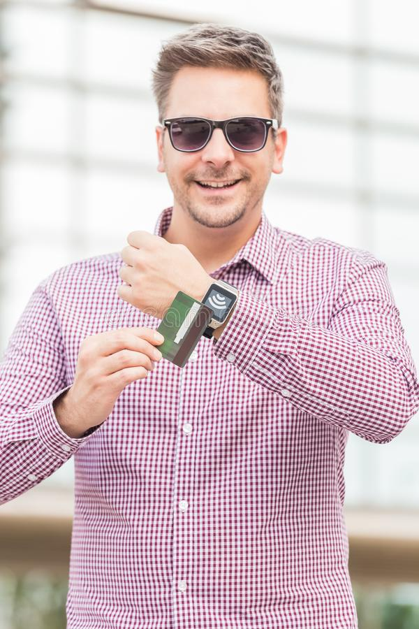 Businessman using wireless payment system with credit card and smart watch in front of business building. Man making payment by using smartwatch and debit card royalty free stock images