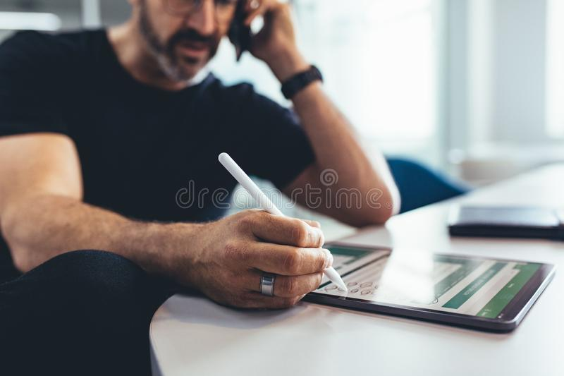 Businessman verifying reports on digital tablet stock images