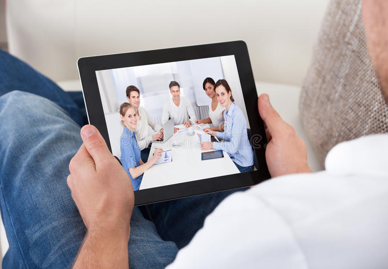 Businessman on a video call chatting to colleagues royalty free stock photography