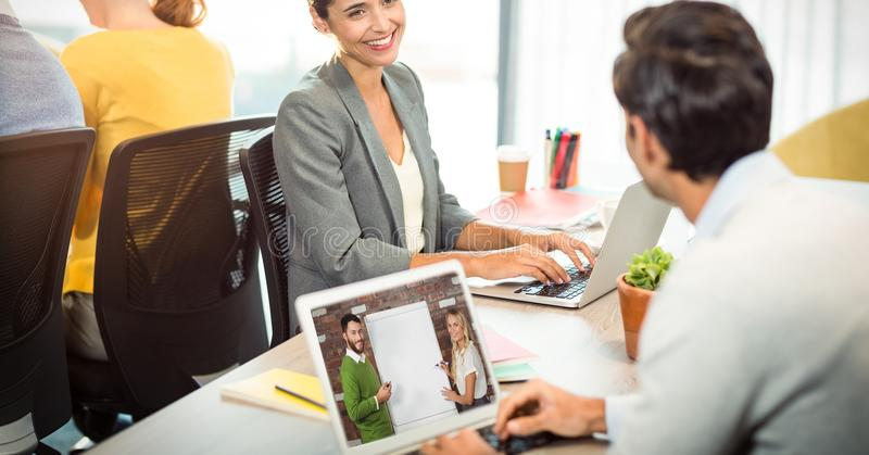 Businessman video conferencing on laptop while looking at colleague in office royalty free stock photography