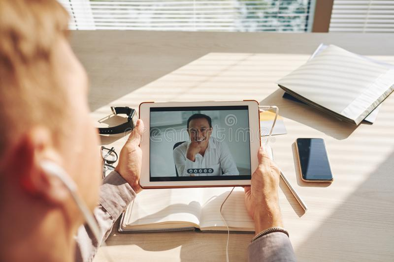 Online communication. Businessman video conferencing with leader on digital tablet at desk in office stock photo
