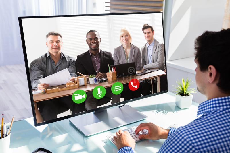 Businessman videoconferencing with his colleagues. On computer at workplace royalty free stock photos