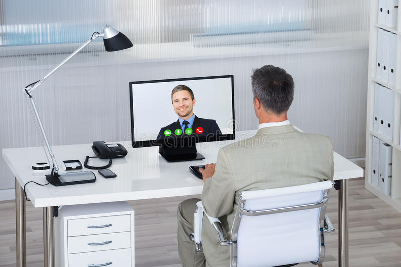 Businessman Videoconferencing With Partner On Computer At Desk stock photos