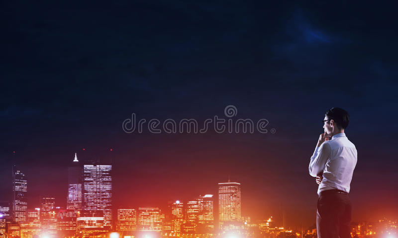 Businessman viewing night glowing city. Elegant businessman with suitcase looking at night city royalty free stock photo