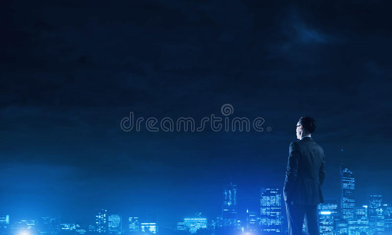 Businessman viewing night glowing city. Elegant businessman with suitcase looking at night city stock photos