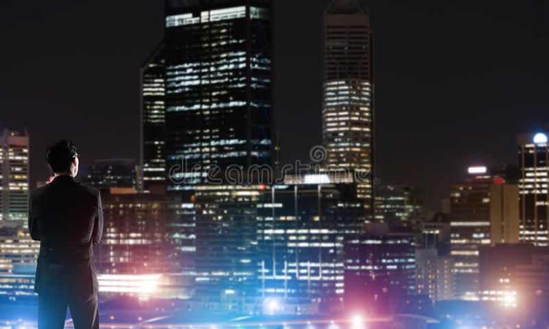 Businessman viewing night glowing city. Elegant businessman with suitcase looking at night city royalty free stock photography