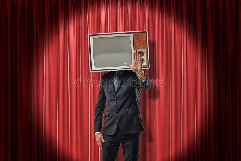 Businessman with vintage tv set instead of head making stop gesture on red stage curtains background. Vintage vehicles. Technologies and communication. Body stock photo