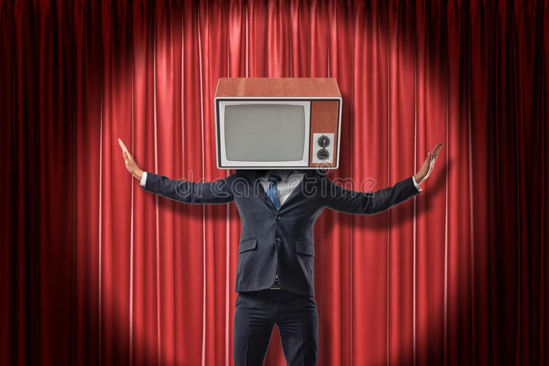 Businessman with vintage tv set instead of head raising arms on red stage curtains background. Vintage vehicles. Technologies and communication. Digital art stock photos