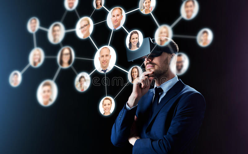 Businessman in virtual reality headset over black stock photo
