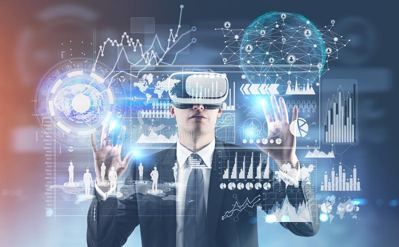 Businessman in VR glasses, infographics, HUD. Young businessman wearing a suit and VR glasses and interacting with what he sees. HUD and infographics. Toned stock photos