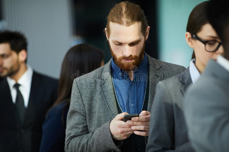 Businessman waiting in line. Serious thoughtful young businessman with beard using telephone while checking message and waiting in line royalty free stock image