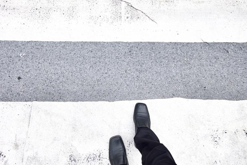 Businessman walking across the crosswalk. Black leather shoes and black slacks. Top view. stock photos