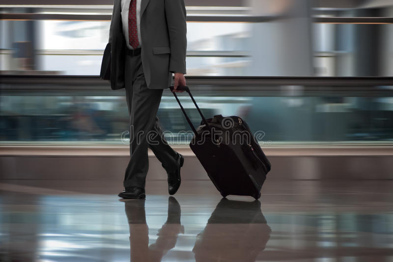 Businessman walking in airport with suitcase stock photography