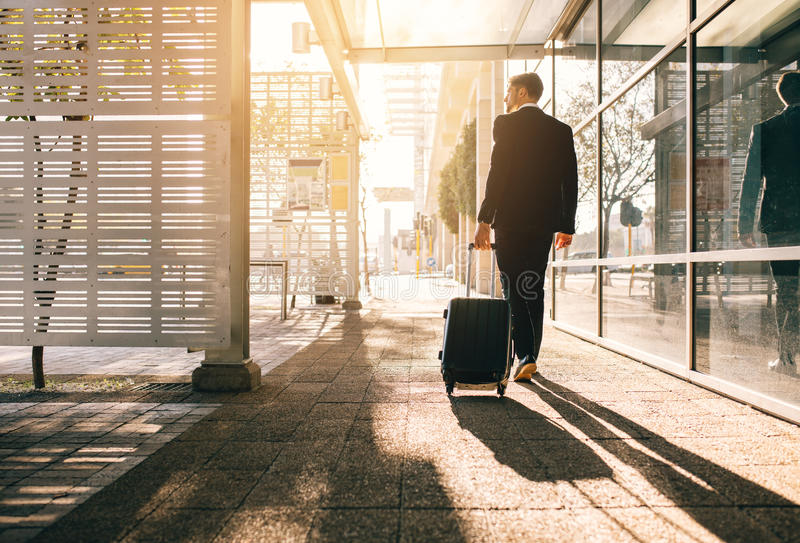 Businessman walking with bag outside airport stock images