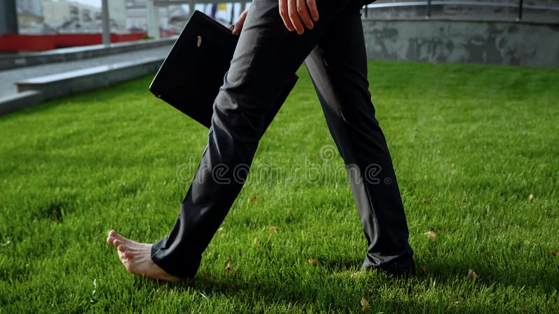 Businessman walking barefoot on green grass near office center, relaxation royalty free stock photos