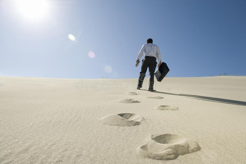 Download Businessman Walking With Briefcase In Desert Stock Image - Image: 29665281