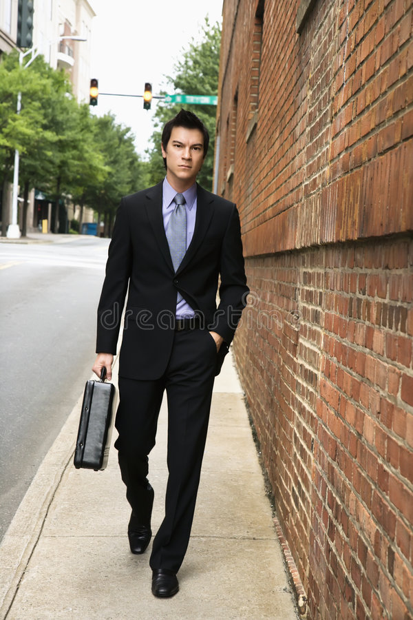 Businessman walking in city. stock image